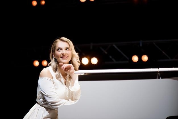 Pianista posando perto de piano branco no palco