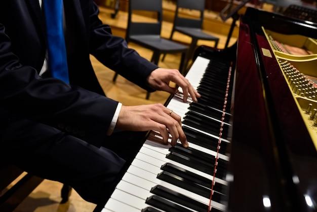 Pianista profissional que executa uma parte em um piano de cauda.