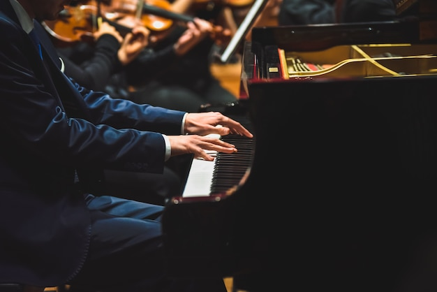 Pianista tocando uma peça em um piano de cauda em um concerto, visto de lado.