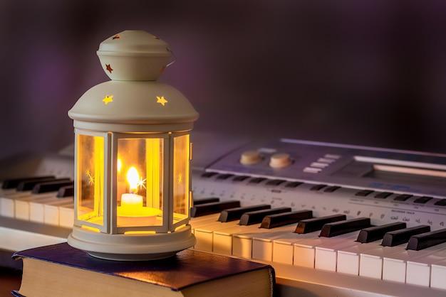 Piano à luz de uma lanterna com uma vela à noite