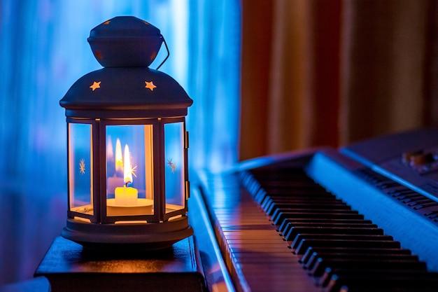 Piano à luz de uma lanterna com uma vela contra a janela à noite