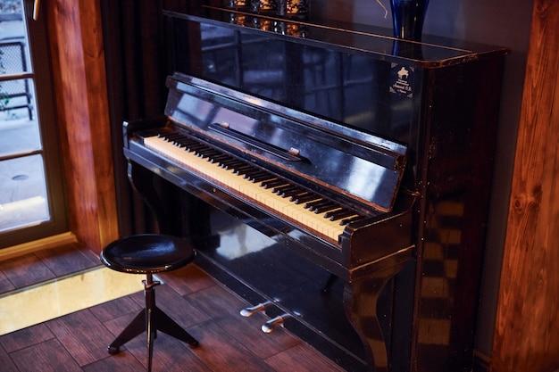 Piano e cadeira dentro de um restaurante moderno sem pessoas dentro.