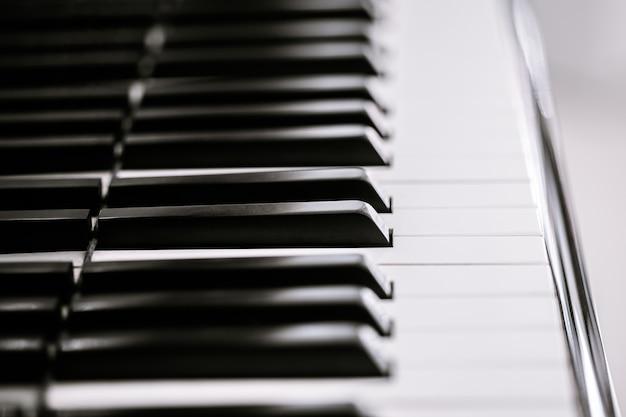Piano e teclado de piano, instrumento musical. chave preta e branca. vista lateral da ferramenta musical do instrumento.