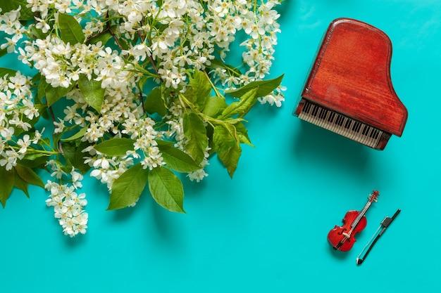 Piano em miniatura e violino com galhos de cerejeira desabrochando. vista superior, close-up em fundo azul claro