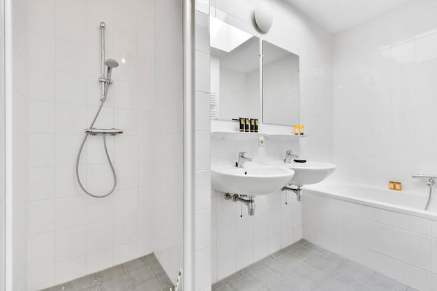 Pias com espelhos e banheira limpa localizadas perto do box com porta de vidro em banheiro moderno com paredes de azulejos brancos