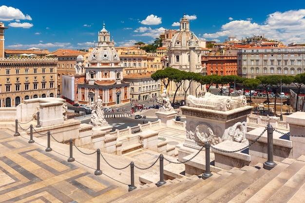 Piazza venezia, ruínas antigas do fórum de trajano, coluna de trajano e igrejas de santa maria di loreto e do santíssimo nome de maria visto do altar da pátria em roma, itália