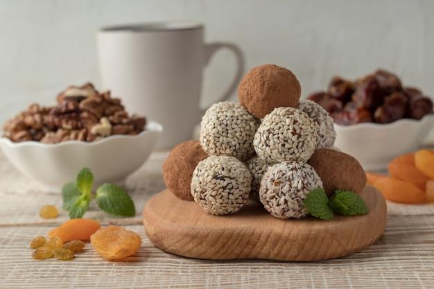 Picadas de energia com cacau em pó, sementes de gergelim e flocos de coco na mesa de madeira branca