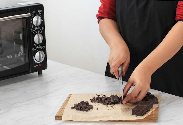 Picar a preparação de blocos de chocolate para cozinhar escuro assar na cozinha