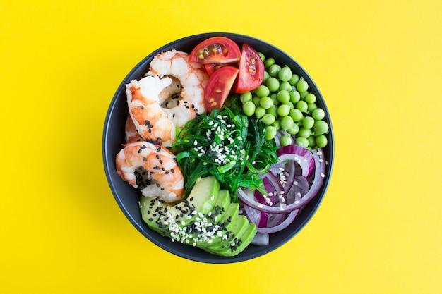 Picar tigela com camarões e legumes na tigela escura