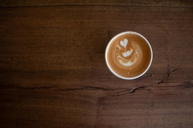 Piccolo latte art em copo de papel na mesa de madeira
