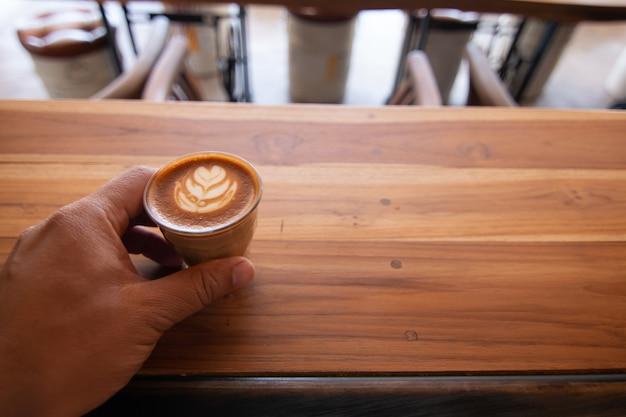 Piccolo latte art em copo pequeno na mesa de madeira