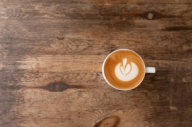 Piccolo latte art em um copo no topo da arte do coração bonito de leite