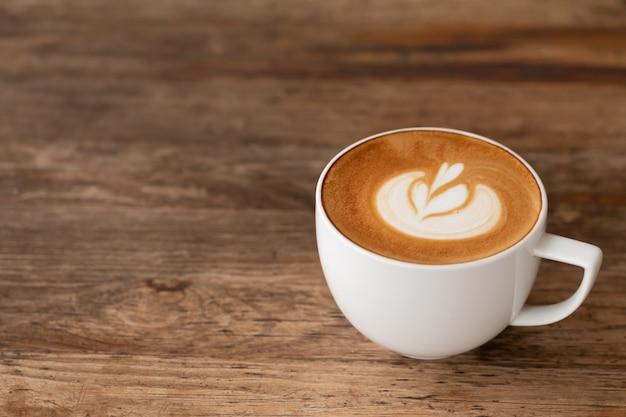 Piccolo latte art em um copo no topo da bela arte do coração de leite na mesa de madeira