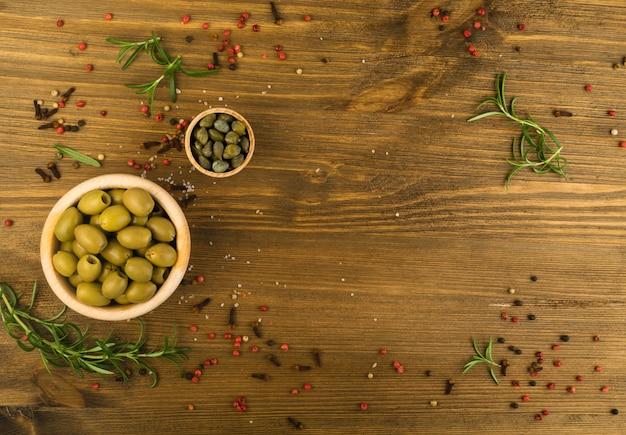 Pickles mistos na vista superior de tigelas de madeira. azeitonas e crapers.