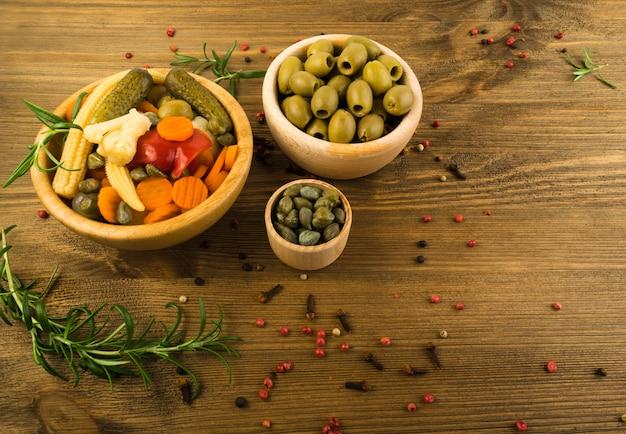 Pickles mistos na vista superior de tigelas de madeira. pepino marinado, cenoura, cebola perl, milho bebê, pimenta vermelha, couve-flor, azeitonas e alcaparras