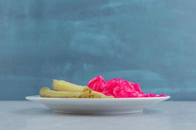 Picles de pepino em fatias ao lado de chucrute em um prato na superfície de mármore