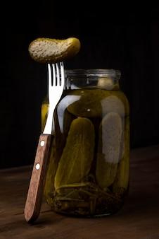 Picles deliciosos em jarra com garfo