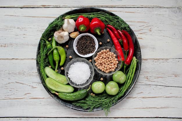 Picles na mesa de madeira branca com verde e vermelho e pimenta, erva-doce, sal, pimenta preta, alho, ervilha, close-up, conceito saudável, vista superior, configuração plana