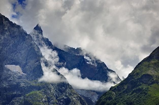 Pico da montanha com geleiras contra a superfície das nuvens e do céu. cume do cáucaso, rússia.