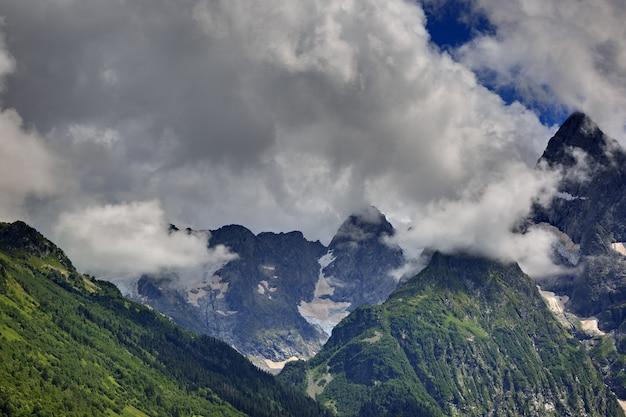 Pico da montanha com geleiras de nuvens e céu. cume do cáucaso, rússia.