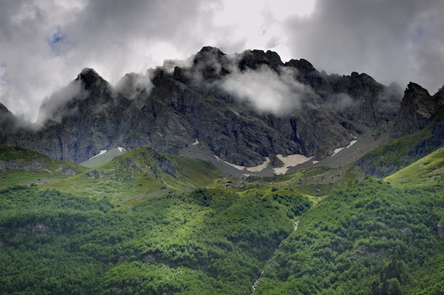 Pico da montanha com geleiras no contexto das nuvens e do céu. cume do cáucaso, rússia.