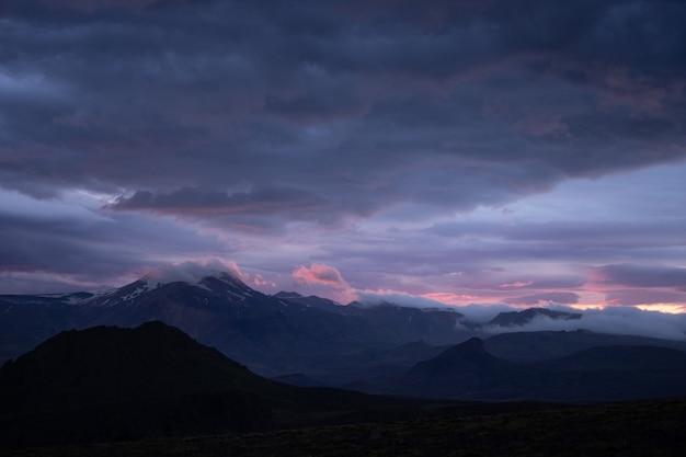 Pico da montanha com neve e nuvens durante o pôr do sol dramático e colorido.