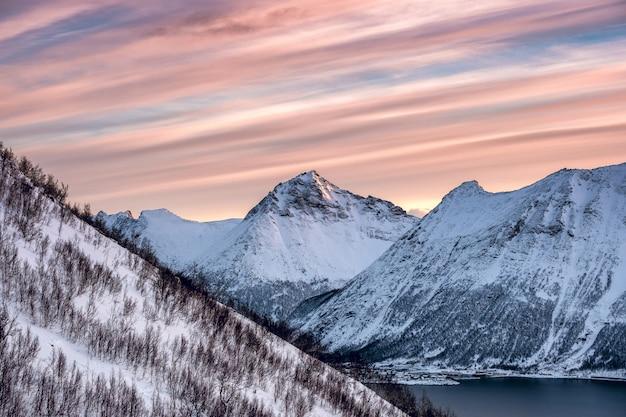 Pico de montanha de neve com céu colorido raia