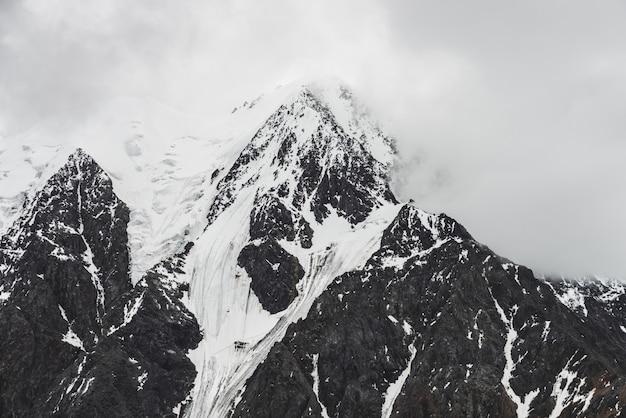 Pico de montanha de neve em nuvens baixas