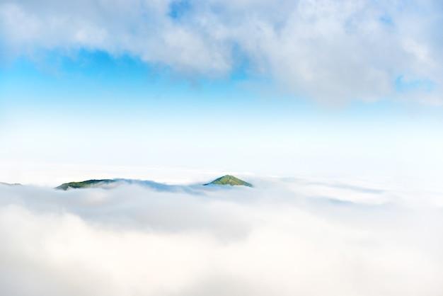 Pico de montanha verde no oceano de nuvens