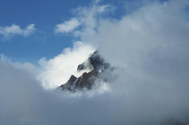 Pico do monte nas nuvens no himalaia