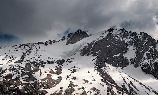 Pico nevado nas montanhas sob as nuvens.
