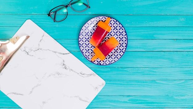 Picolés brilhantes na placa e óculos e suporte para papéis na superfície de madeira