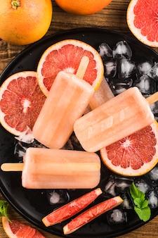 Picolés caseiros de toranja vermelha com cubos de gelo.