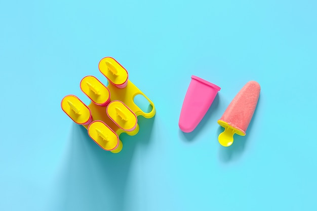 Picolés caseiros. sorvete de morango natural em moldes de plástico brilhante