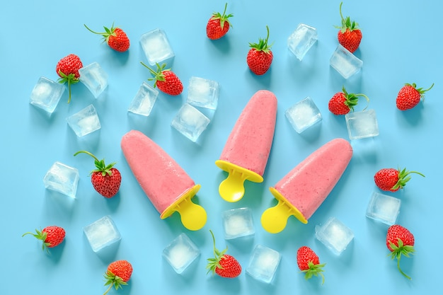 Picolés caseiros. sorvete natural em moldes de plástico brilhantes, morangos e cubos de gelo