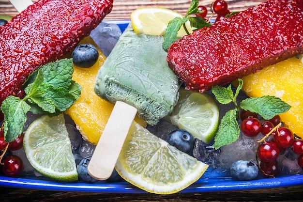 Picolés com frutas e bagas em uma mesa de madeira
