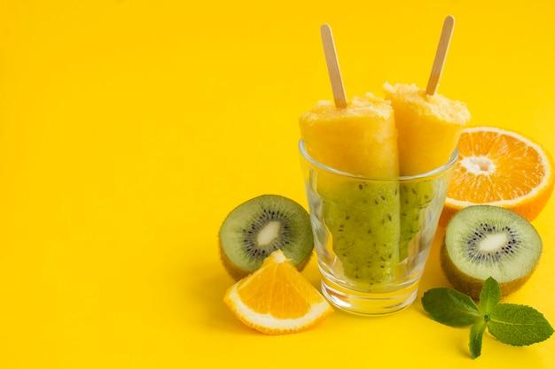 Picolés com kiwi e fruta laranja. copie o espaço.