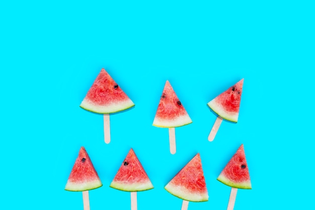 Picolés de fatia de melancia sobre fundo azul.