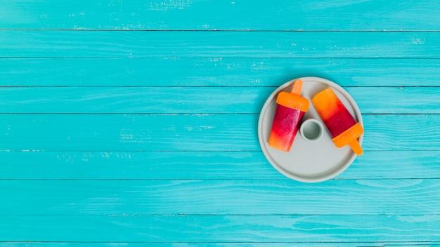Picolés de frutas brilhantes no prato na superfície de madeira