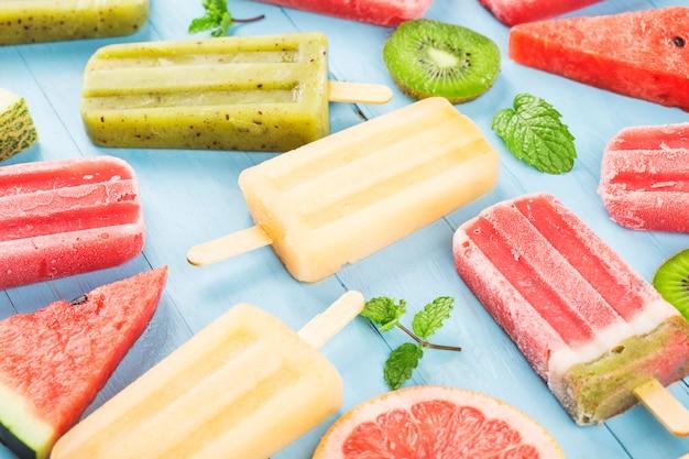 Picolés de frutas inteiras saudáveis com melancia e melancia de kiwi na mesa de madeira vintage