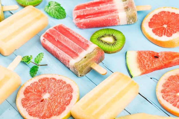 Picolés de frutas inteiras saudáveis com melão de melancia de kiwi e frutas vermelhas na mesa de madeira vintage