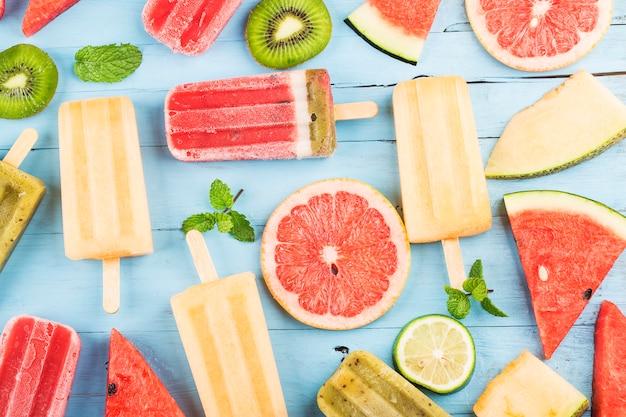 Picolés de frutas inteiras saudáveis com melão de melancia kiwi bagas na mesa de madeira vintage