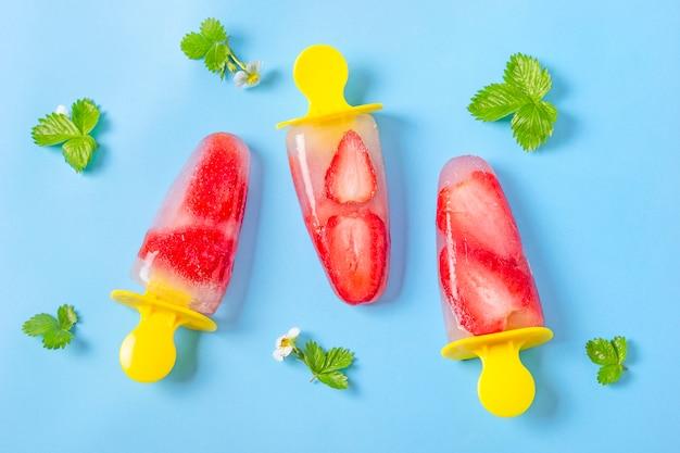 Picolés de morango caseiros suco congelado, palitos de sorvete no fundo azul