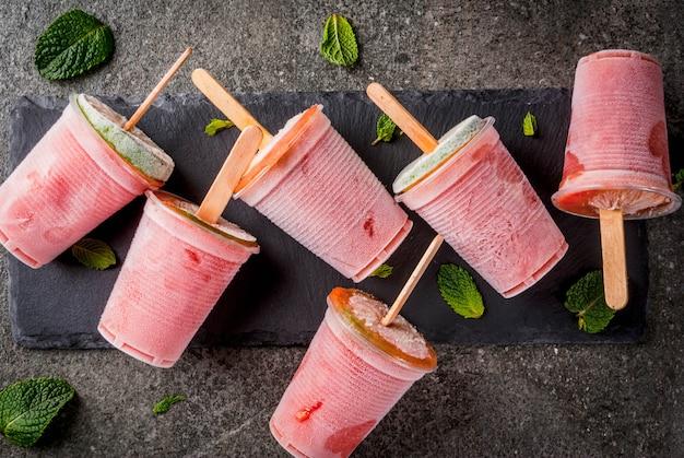 Picolés de sorvete caseiro. bebidas congeladas. cocktail congelado de melancia ou bagas, hortelã e limão.