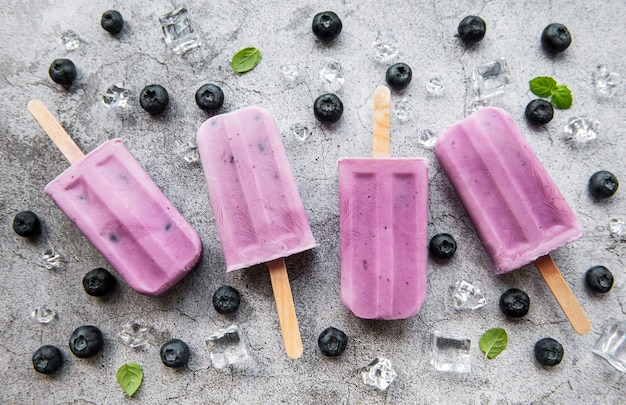Picolés de sorvete de iogurte caseiro e mirtilos orgânicos frescos.