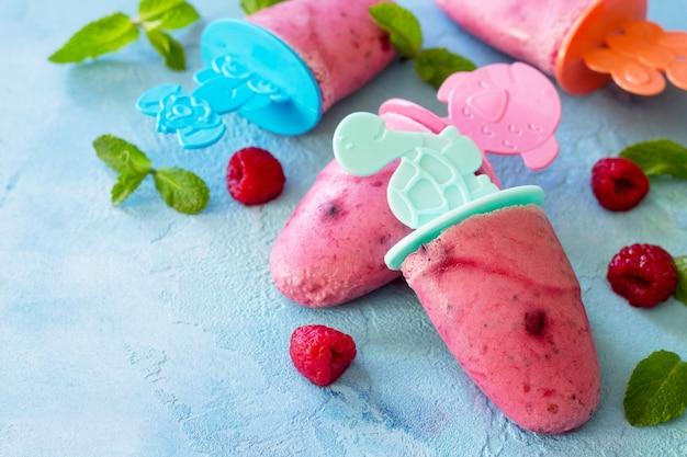 Picolés de sorvete infantil sorvete de rasberry no fundo azul de concreto copiar espaço