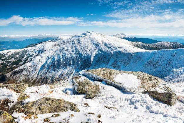 Picos brancos de montanhas com pedras na neve. paisagem de inverno