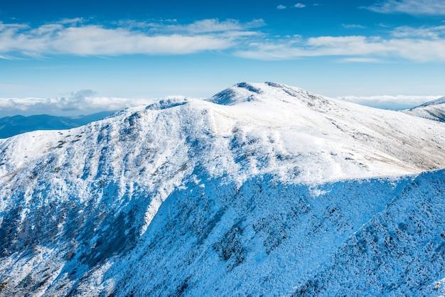 Picos brancos de montanhas na neve. paisagem de inverno