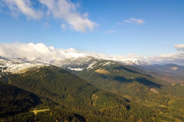 Picos de altas montanhas cobertos com floresta de abetos de outono e altos picos nevados.
