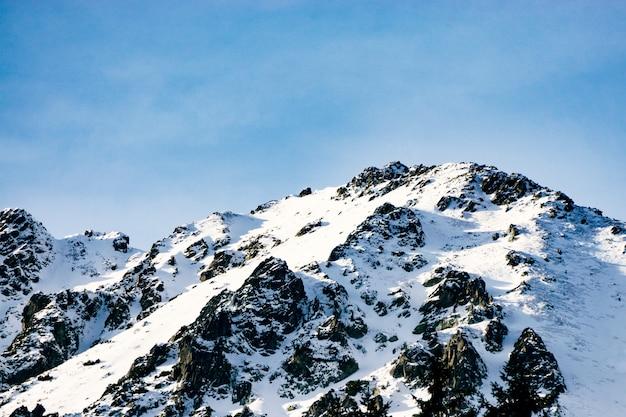 Picos de montanhas bonitas cobertas de neve. nuvens tocam o topo das montanhas. férias de inverno